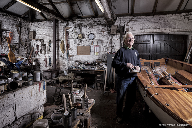 Boat Builder next to dinghy with plane in hand © Paul Worpole Photography