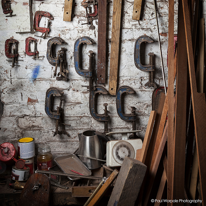 Boat Builder workshop showing G clamps on a white brick wall © Paul Worpole Photography