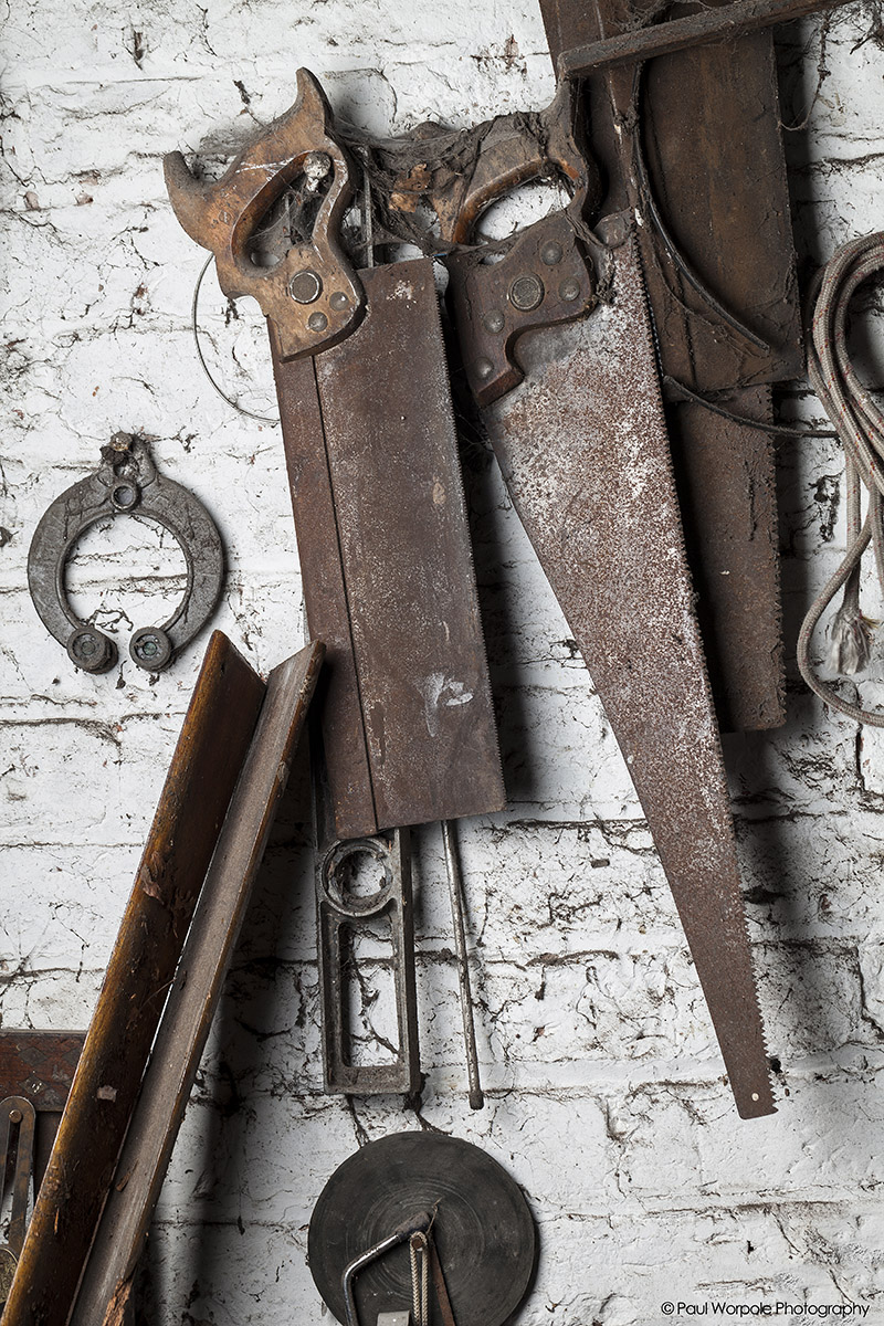 Boat Builder workshop showing rusty old saws on a white brick wall © Paul Worpole Photography