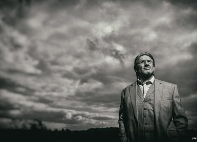 Portrait of Man in field with dark clouds behind © Paul Worpole Photography