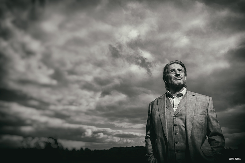 Conceptual Portrait of Man in field with dark clouds behind © Paul Worpole Photography