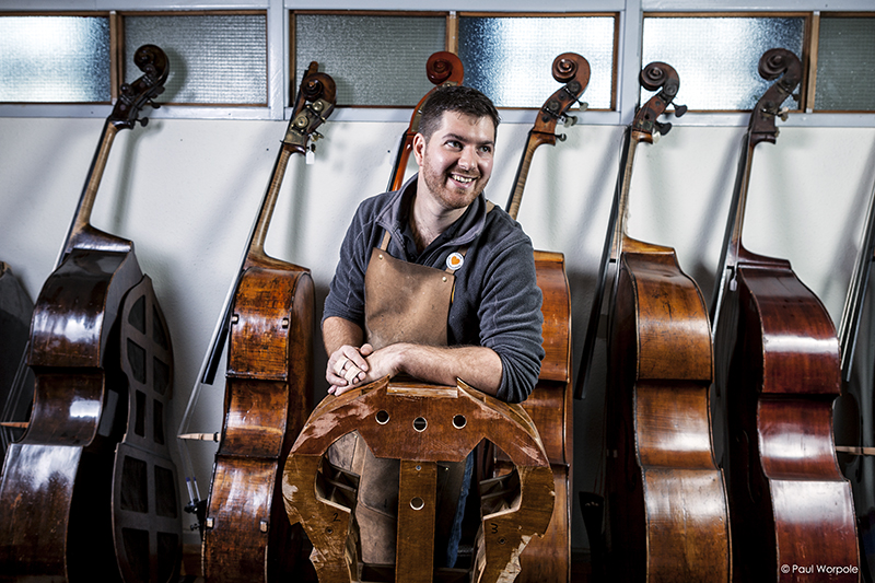 Sam Wells Bass Maker stands next to form with six basses behind him © Paul Worpole Photography