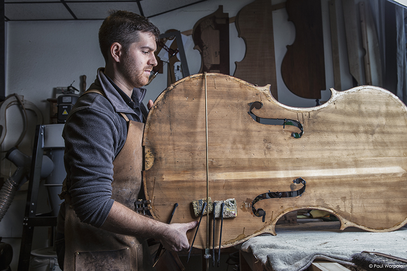 Sam Wells Bass Maker alighning clamps on f holes © Paul Worpole Photography