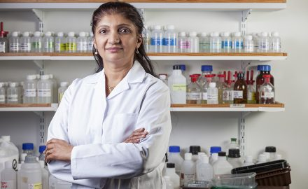 Staff Headshot Photography of woman chemist standing in Lab with lab coat on in front of bottles© Paul Worpole Photography