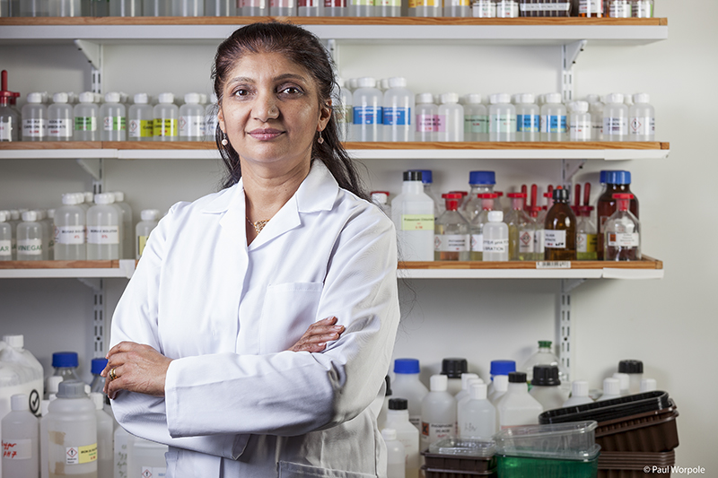 Editorial Photography of woman chemist standing in front of bottles© Paul Worpole Photography