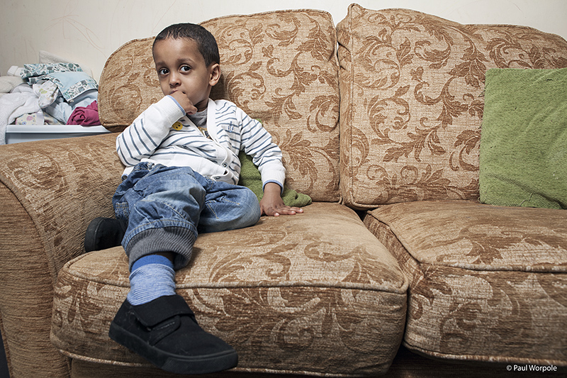 Editorial Photography of young boy on couch with plimsolls © Paul Worpole Photography
