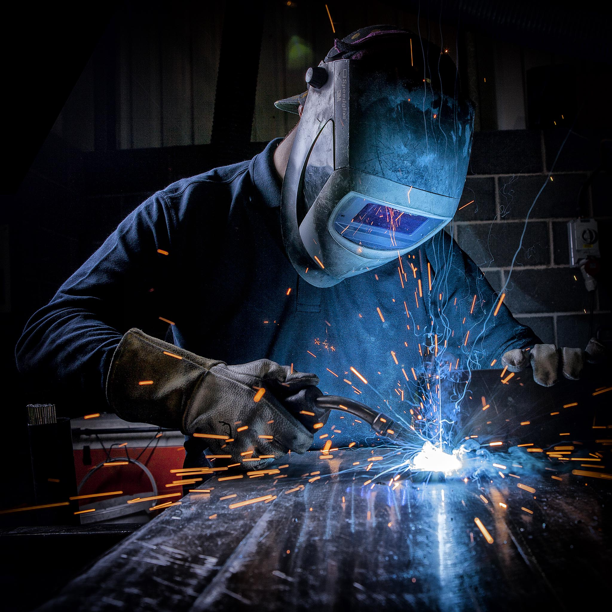 Industrial photography of man in welding mask with sparks flying © Paul Worpole Photography