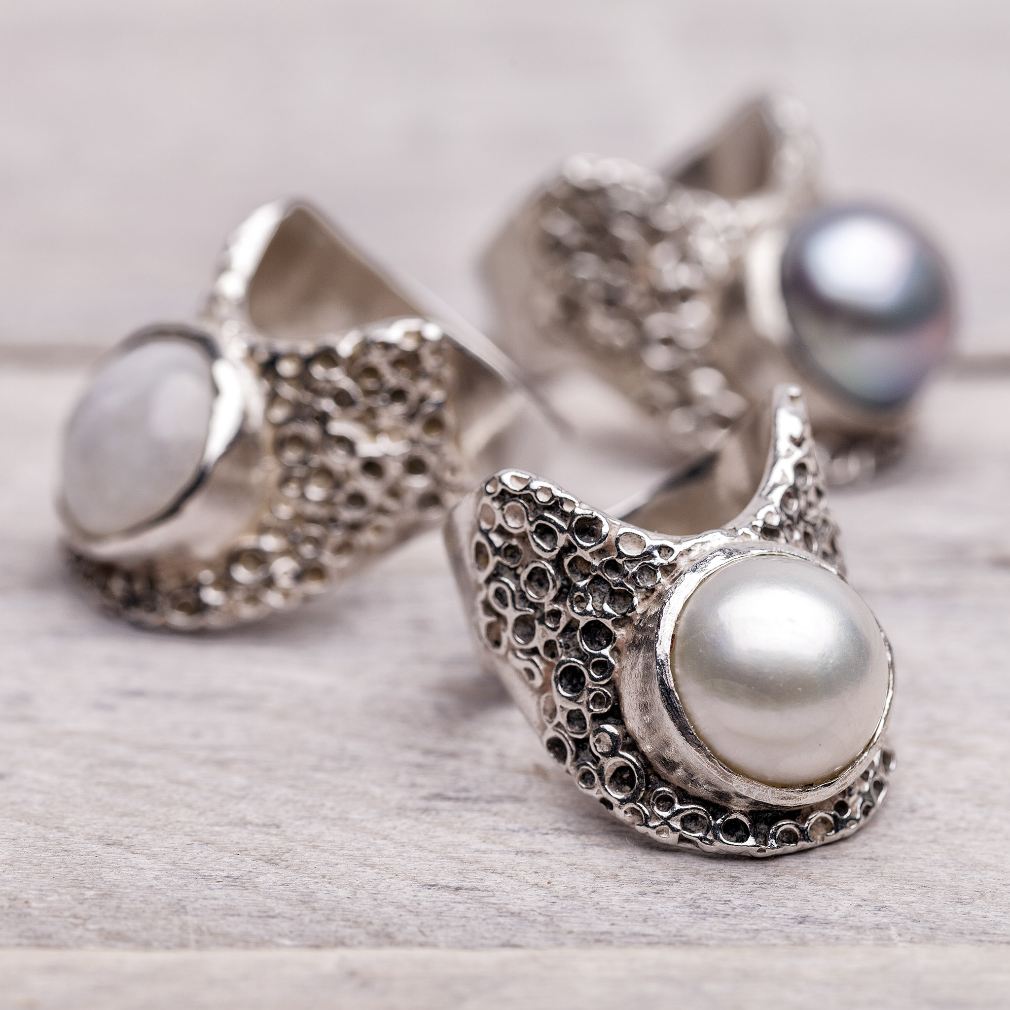Product shot of three pearl and silver rings on pale wood © Paul Worpole Photography