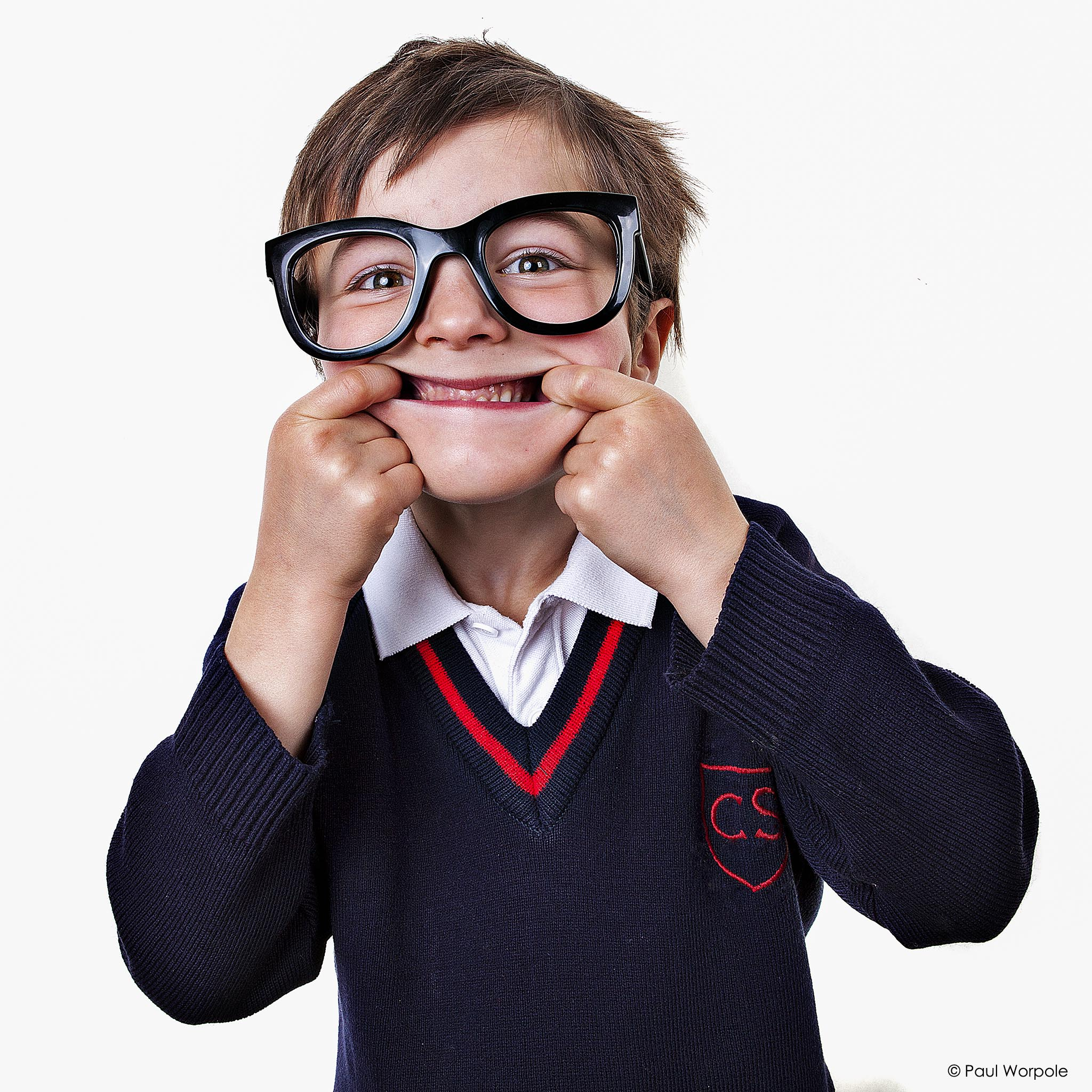 Commercial photography of school boy with huge black frame glasses pulling a wide mouth face © Paul Worpole Photography