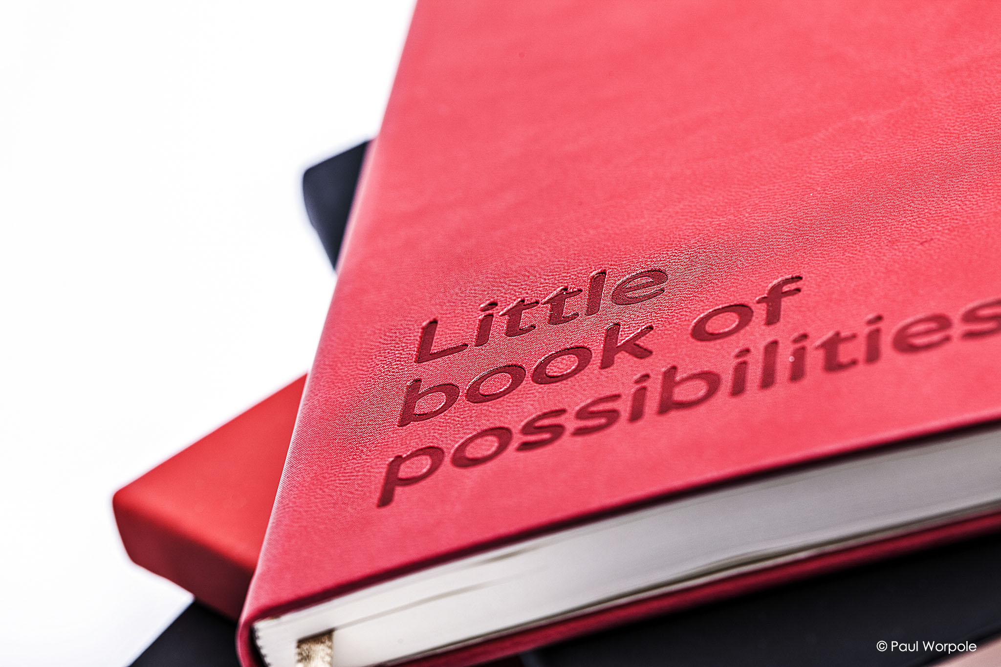 Advertising photography of red leather note book with Little book of possibilities embossed on cover © Paul Worpole Photography