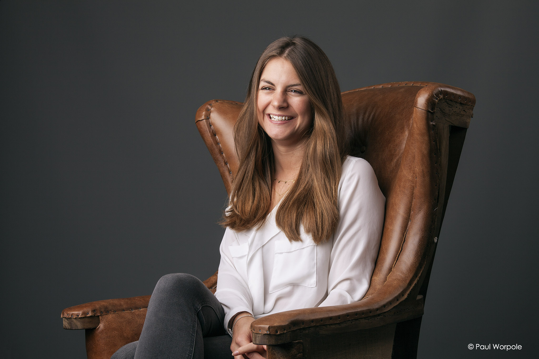 Staff headshot photography of a smiling woman in brown leather chair © Paul Worpole Photography