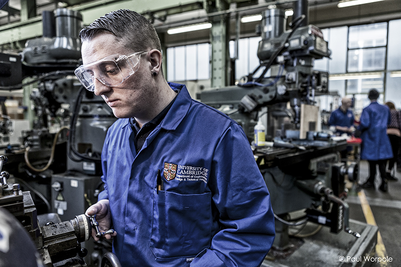 Staff Headshot Portrait of a man in a blue University of Cambridge boiler suit working on a lathe © Paul Worpole Photography