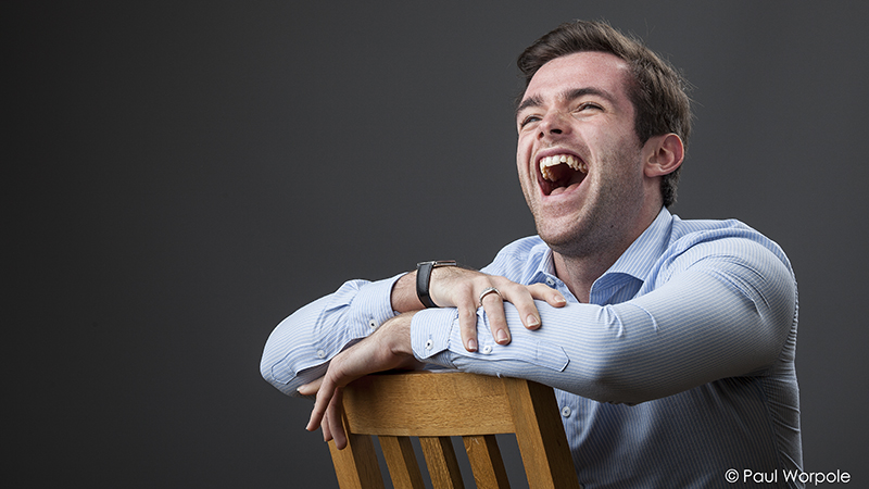 Staff Headshot Portrait of Man leaning on a chair back laughing in blue shirt© Paul Worpole Photography