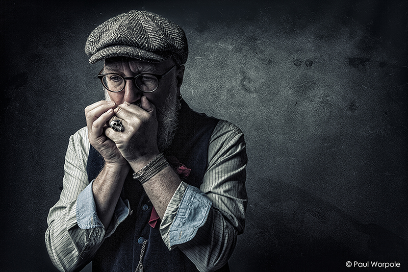 Staff Headshot Portrait of Man playing harmonica with herringbone baker boy flat cap on with a skull head ring and glasses on © Paul Worpole Photography