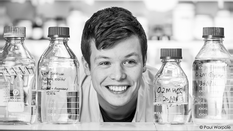 Staff Headshot Portrait of a man scientist smiling in between lab glass jars © Paul Worpole Photography