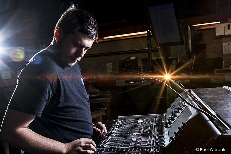 Staff Headshot Portrait of a man in a black t-shirt at a light mixing desk © Paul Worpole Photography