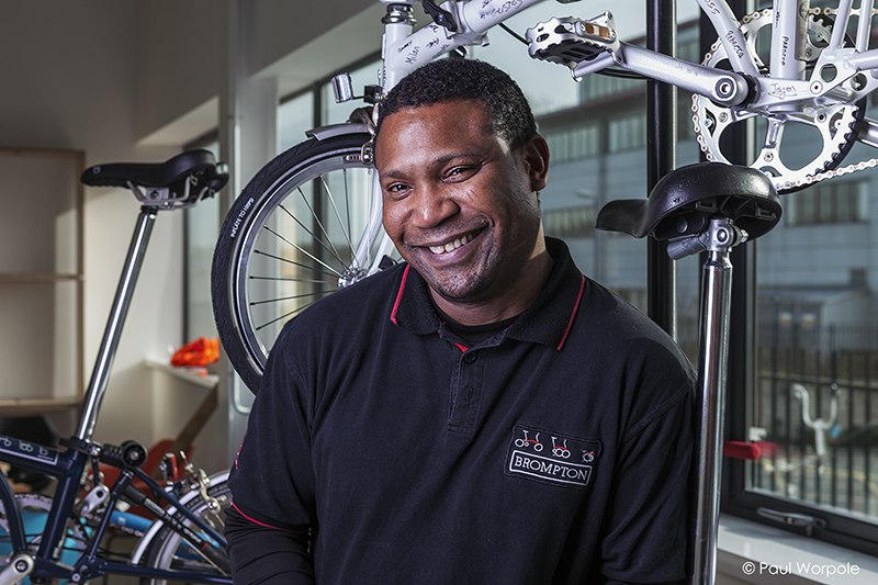 Staff Headshots portrait of a man in Brompton Bikes smailing with bikes around him © Paul Worpole Photography