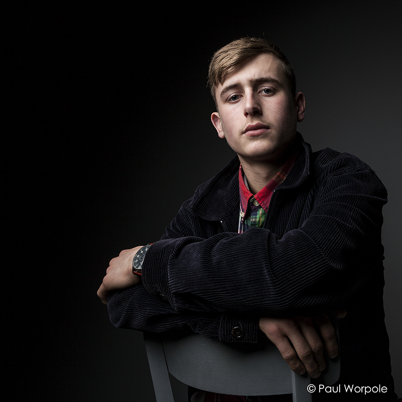 Staff Headshots portrait of a young man in a corduroy jacket leaning on a back of a chair © Paul Worpole Photography