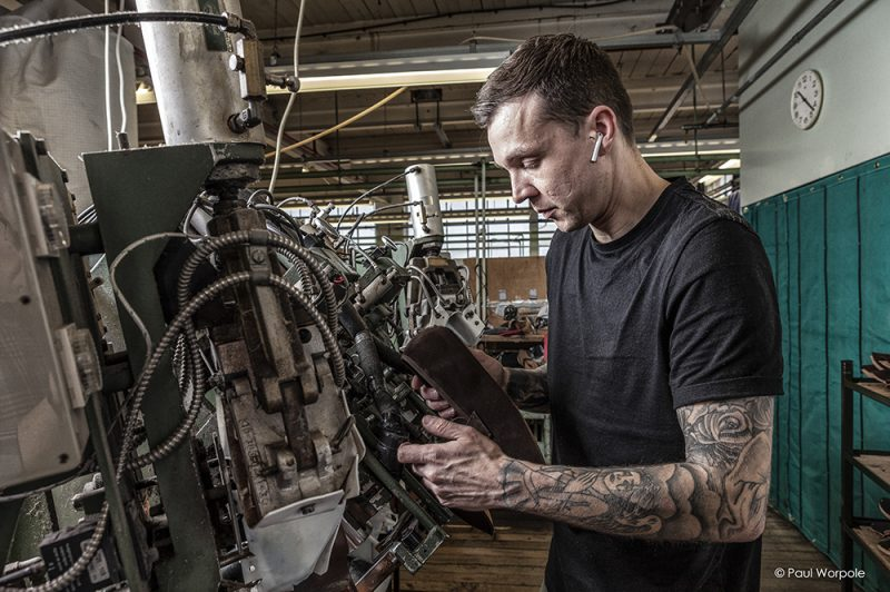 10 Essential photographs that every company should have in their portfolio. Portrait of man working on a shoe machine with tattoos © Paul Worpole Photography