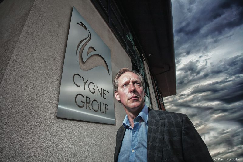 10 Essential photographs that every company should have in their portfolio. Portrait of man against logo of Cygnet group © Paul Worpole Photography